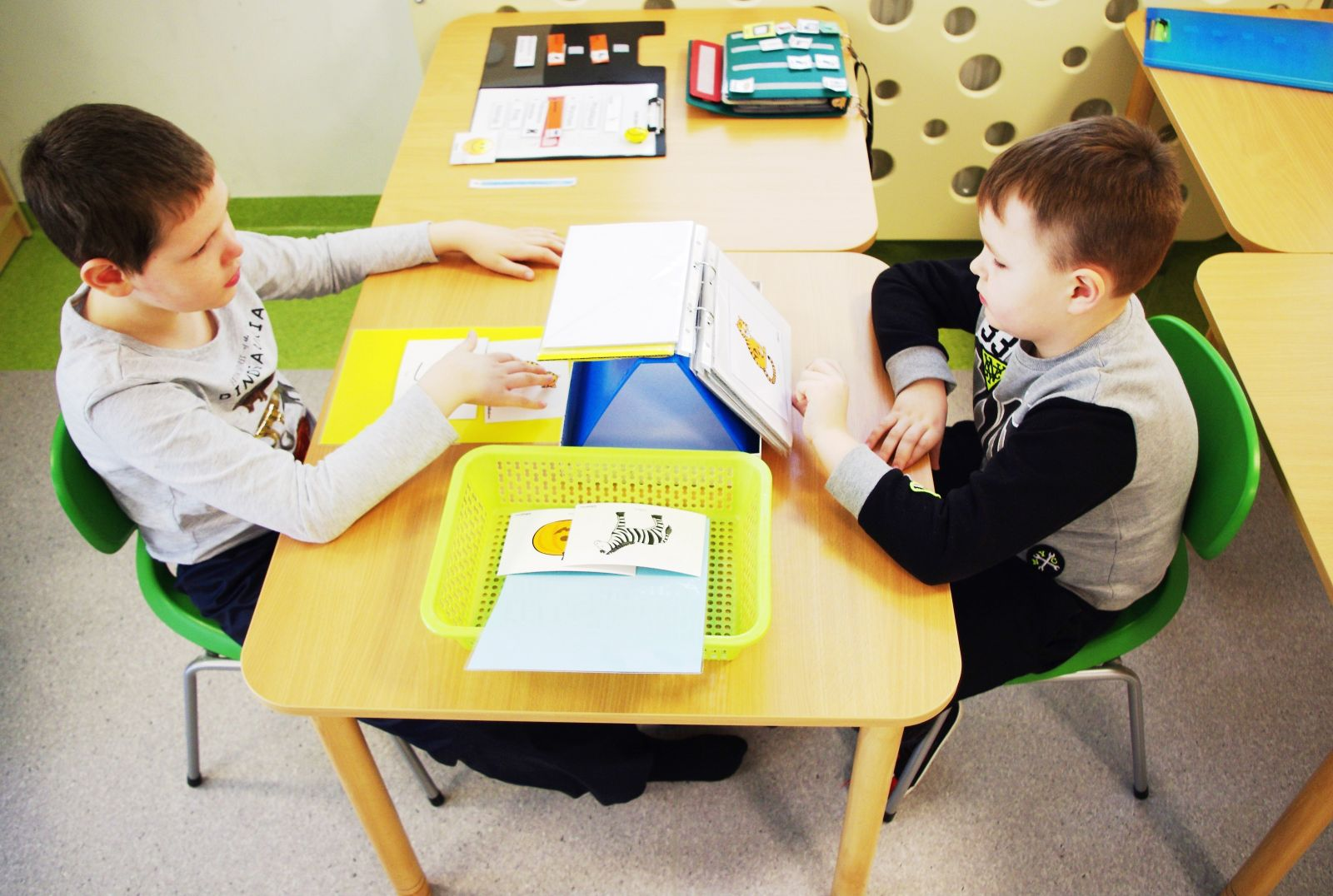 dwoje dzieci siedzi na przeciwko siebie przy stoliku i uczą się języka obrazkowego, czyli alternatywnych metod komunikacji